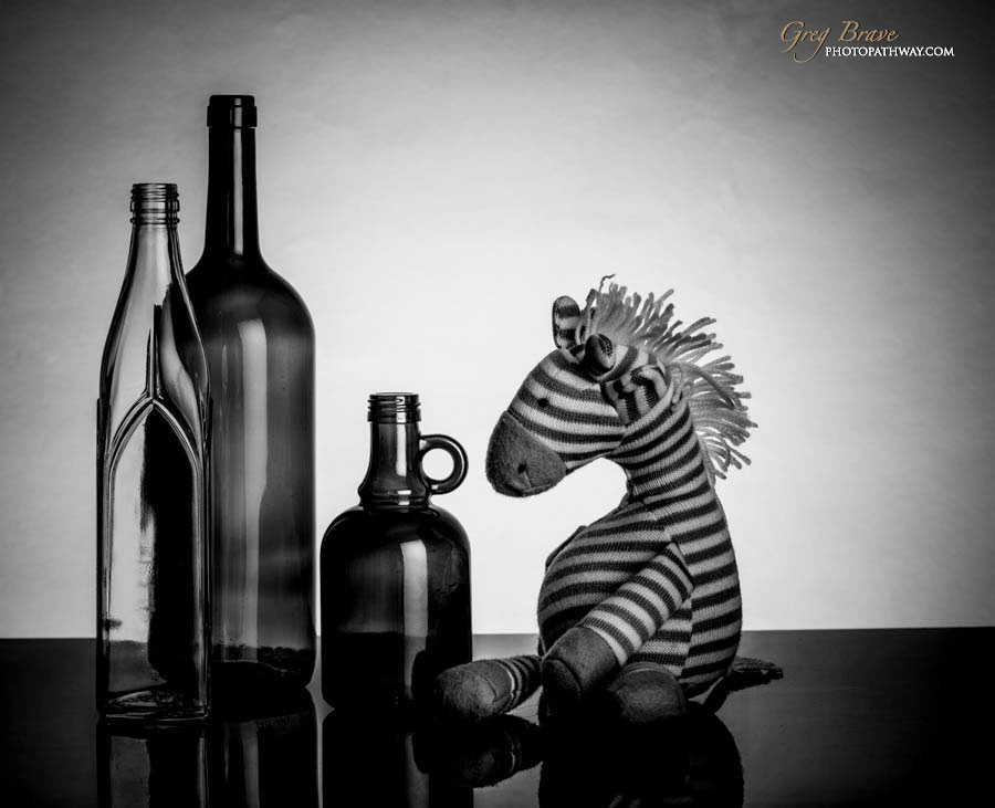 Still life with bottles and toy horse in black and white by greg brave