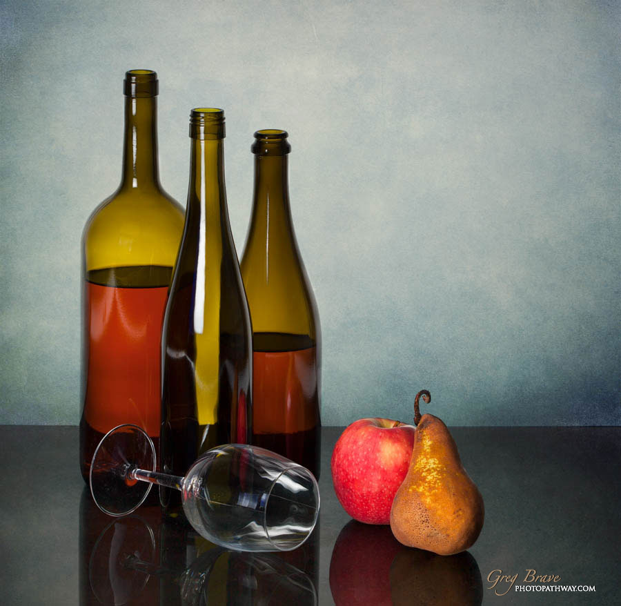 Still life with bottles glass and fruits in color by greg brave