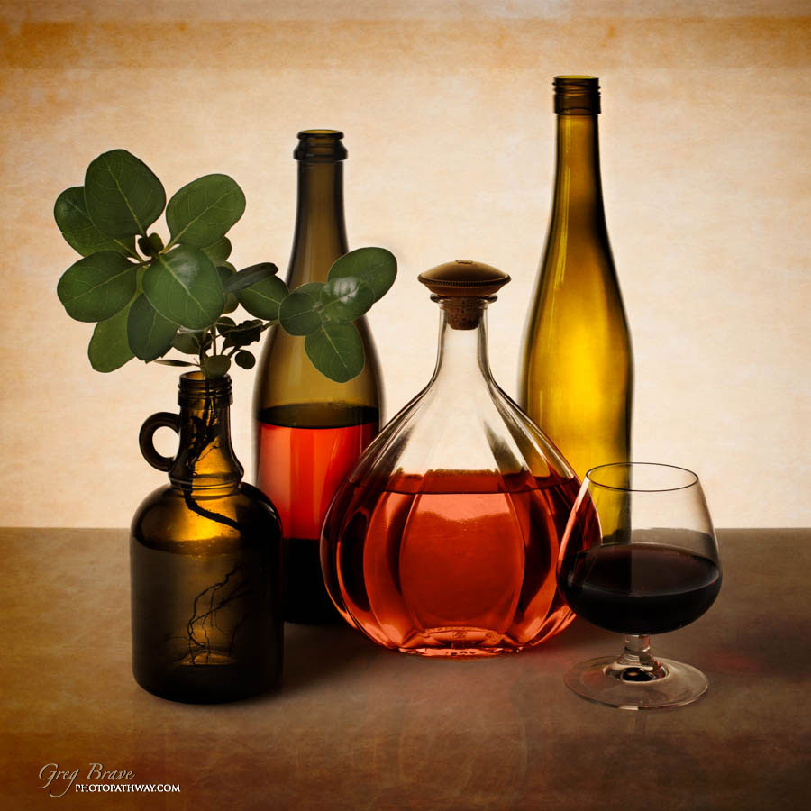 Still life with bottles glass and flora in color by greg brave