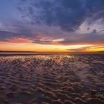 Beautiful glowing sunset reflections in sand ripples, at Inverloch Foreshore Beach, Gippsland, Victoria, Australia