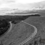 Winding road along Cardinia Reservoir dam wall in black and white. Melbourne, Australia.