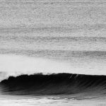 Closeup of a breaking wave in black and white