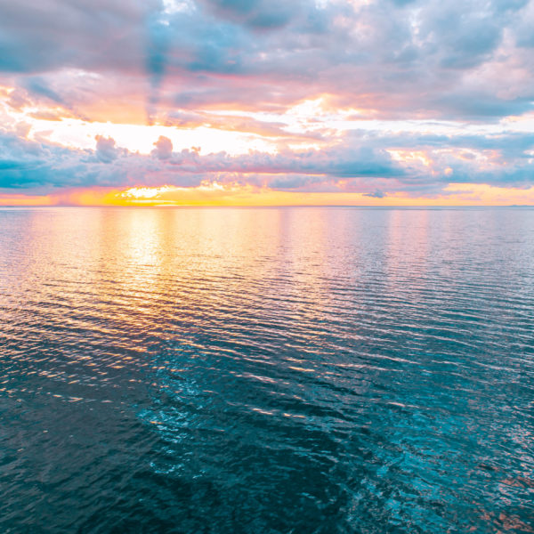 Minimalistic seascape at beautiful sunset - sun, clouds, and calm water surface