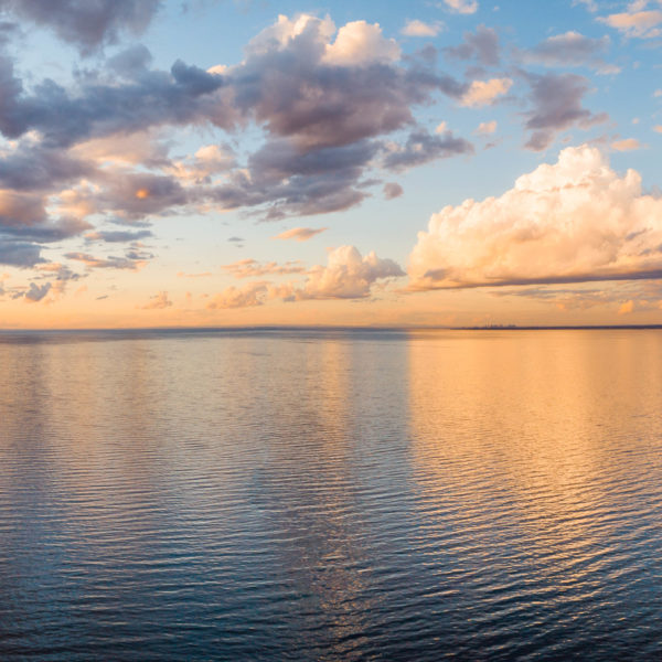 Clouds reflecting in calm sea at golden sunset - minimalist aerial panorama