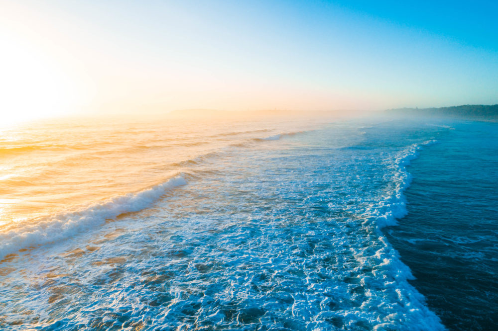 Beautiful golden sunrise over blue ocean waves with copy space