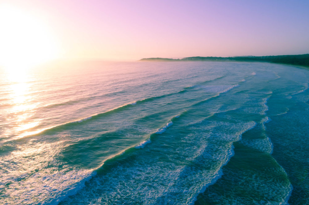 Vivid sunrise over ocean coastline - aerial view