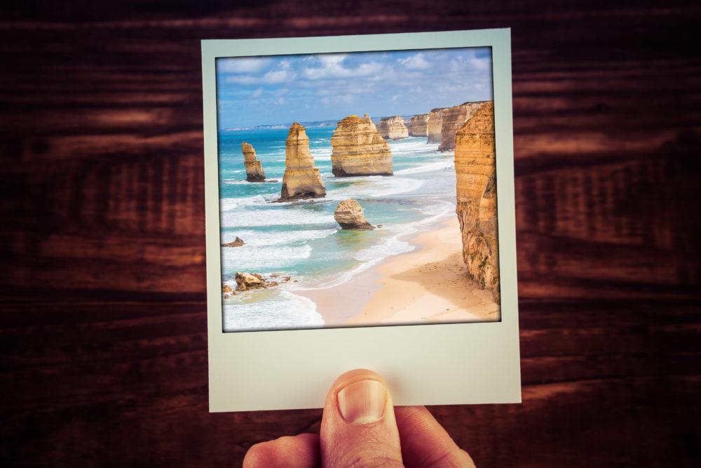 Hand holding photograph of The Twelve Apostles, Great Ocean Road, Australia