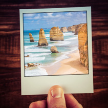 Hand holding photograph of The Twelve Apostles, Great Ocean Road, Australia