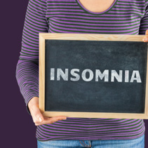 Female hands holding small black chalkboard in front of the body with written words saying Insomnia