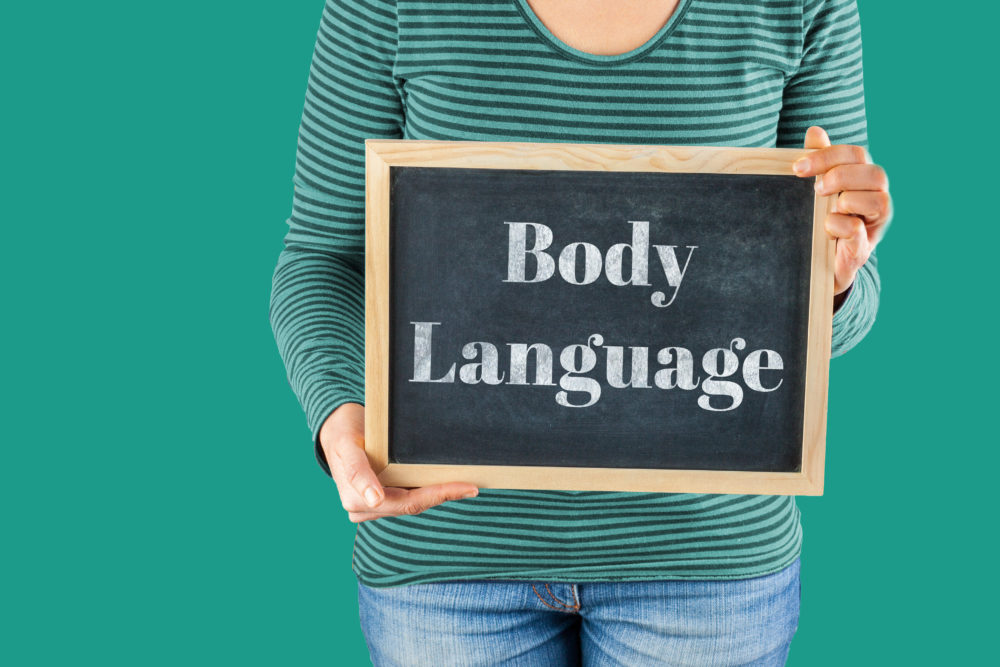 Female hands holding small black chalkboard in front of the body with written words saying Body Language