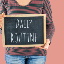 Female hands holding small black chalkboard in front of the body with written words saying Daily Routine