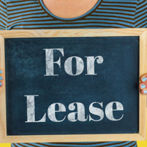 Female hands holding small black chalkboard in front of the body with written words saying For Lease