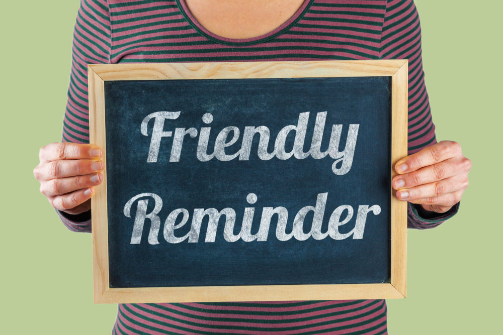 Female hands holding small black chalkboard in front of the body with written words saying Friendly Reminder