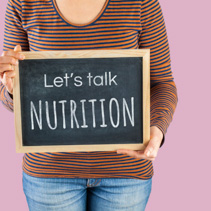 Female hands holding small black chalkboard in front of the body with text saying Let's talk Nutrition