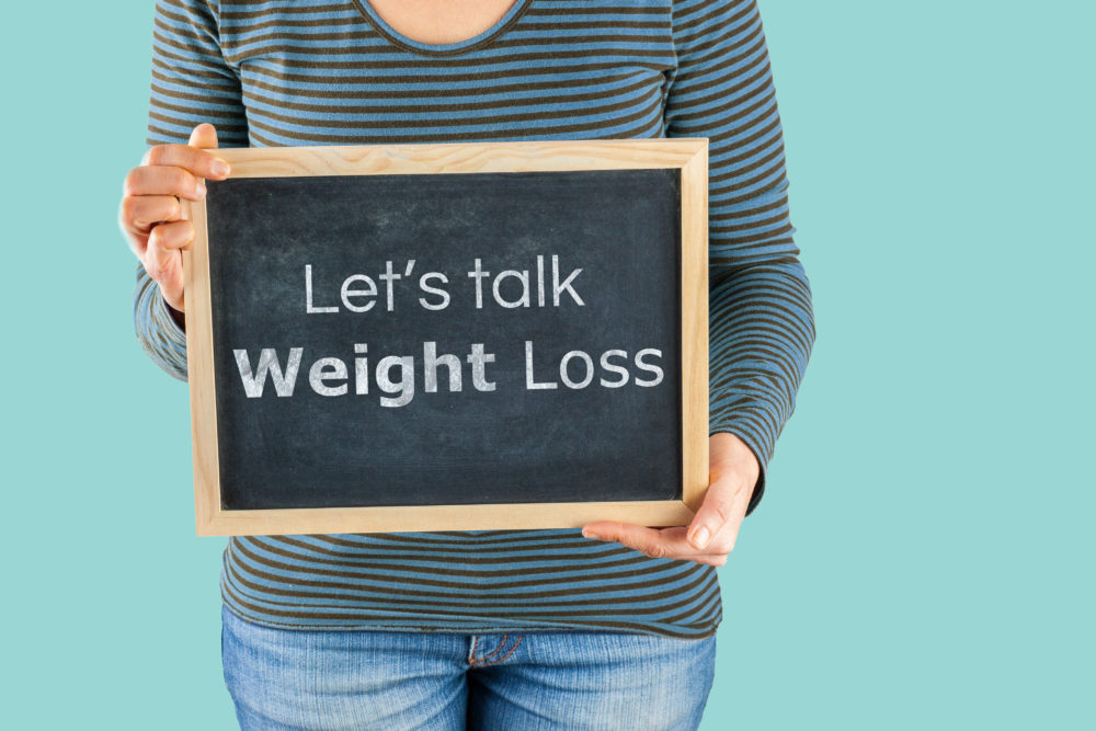 Female hands holding small black chalkboard in front of the body with text saying Let's talk Weight Loss