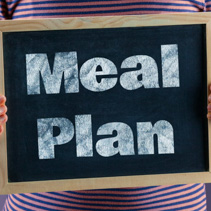 Female hands holding small black chalkboard in front of the body with text saying Meal Plan