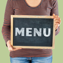 Female hands holding small black chalkboard in front of the body with written words saying Menu