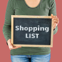 Female hands holding small black chalkboard in front of the body with written words saying Shopping List