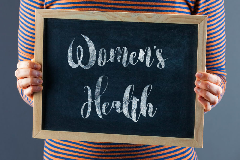 Female hands holding small black chalkboard in front of the body with text saying Women's Health