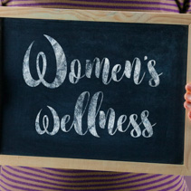 Female hands holding small black chalkboard in front of the body with text saying Women's Wellness