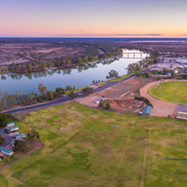 Aerial panorama landscape of Murray River flowing through the town of Berri near sports oval at dusk. Riverland region of South Australia