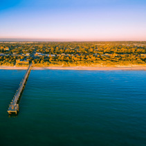 Aerial view of long wooden pier stretching into the ocean and coastal vegetation at sunset