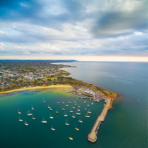 Aerial view of moored boats, pier and coastline at beautiful sunset. Mornington Peninsula, Melbourne, Victoria, Australia