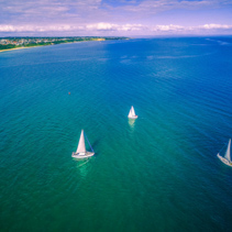 Aerial seascape of sailboats sailing in ocean near coastline