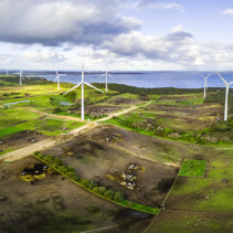 Aerial panorama of stormy clouds above wind turbines and pastures on ocean shore