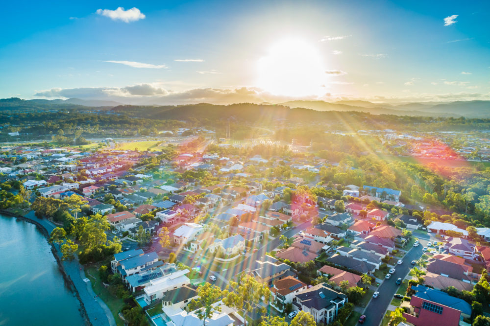 Aerial landscape of Varsity Lakes suburb at sunset with sun rays flare. Gold Coast, Queensland, Australia