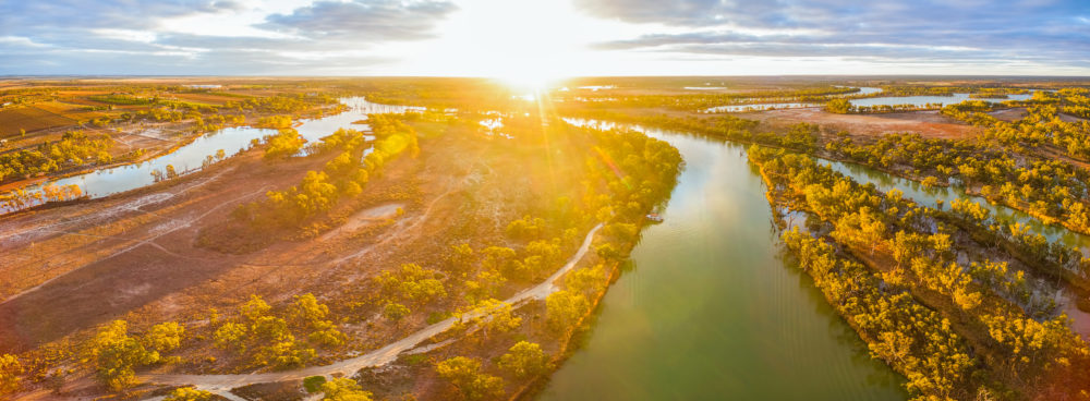 Aerial panorama of bright sun flare at sunset over Murray River in South Australia