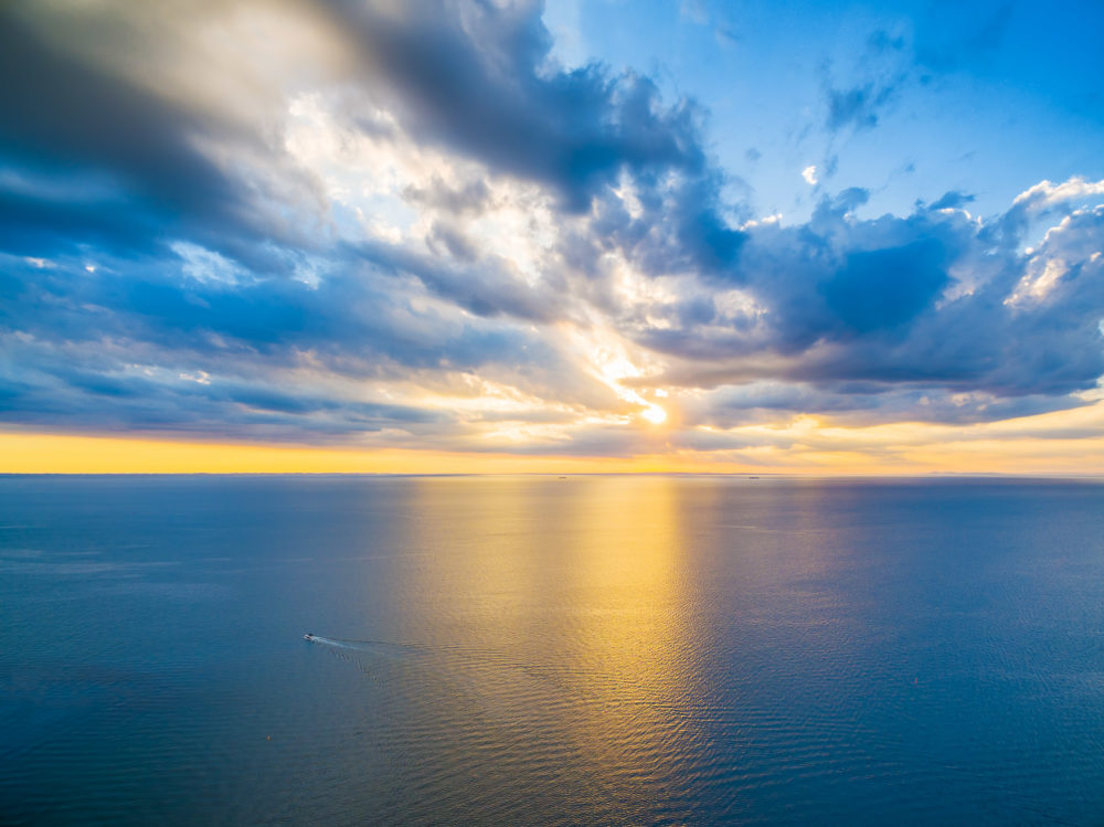 Aerial panoramic view of lonely boat sailing across ocean at beautiful sunset.