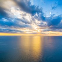 Aerial panoramic view of lonely boat sailing across ocean at beautiful sunset.