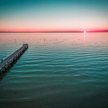 Long wooden pier stretching into the ocean at beautiful sunset