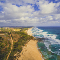 Ocean coastline with rural road and beautiful clouds - aerial landscape of Australia