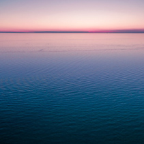 Empty horizon over water at dusk. nothing but water and clear sky.