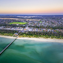Aerial view of long wooden pier stretching into shallow ocean water and coastal suburban houses in Melbourne, Australia