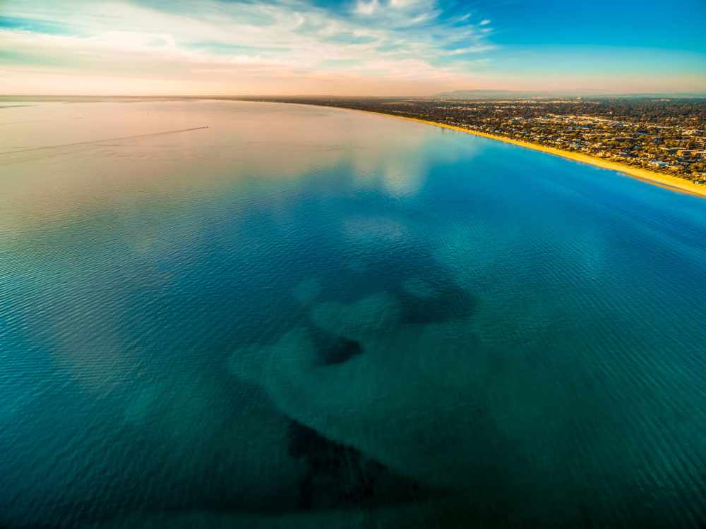 Smooth shallow ocean water surface with cloud reflections near coastline at sunset