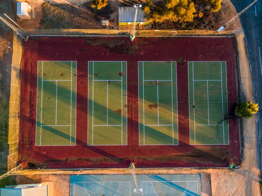 Looking down at old tennis courts at sunset - aerial view