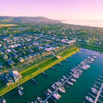 Aerial view of Mornington Peninsula coastline, suburbs, and marina at sunset. Melbourne, Australia