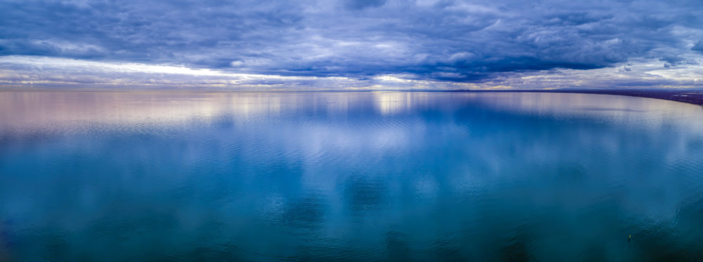 Wide aerial panorama of stormy clouds over smooth ocean water surface