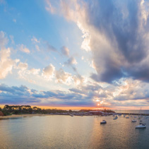 Aerial panorama of Australian coastline with long pier and yachts at beautiful sunset and cloud formations