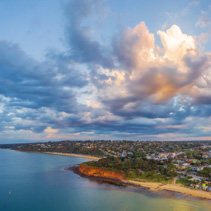 Aerial panorama of coastline, beaches and Australian suburban area at sunset with beautiful clouds. Mornington Peninsula, Melbourne, Victoria, Australia