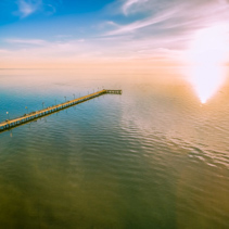 Long wooden pier reaching the sun at magnificent sunset