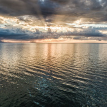 Beautiful sunset over water with sun rays protruding through the clouds