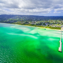 Aerial view of vivid turquoise ocean water and wooden pier at suburbia coastline