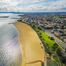 Aerial view of Brighton Beach coastline with Melbourne CBD skyscrapers in the distance