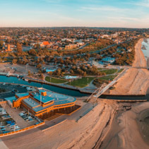 Aerial panorama of Frankston suburb yacht club, footbridge, and pier at sunset. Melbourne, Australia