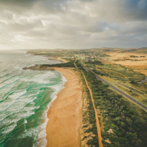 Rural highway passing near beautiful ocean coastline and walking trail in Australia - aerial landscape