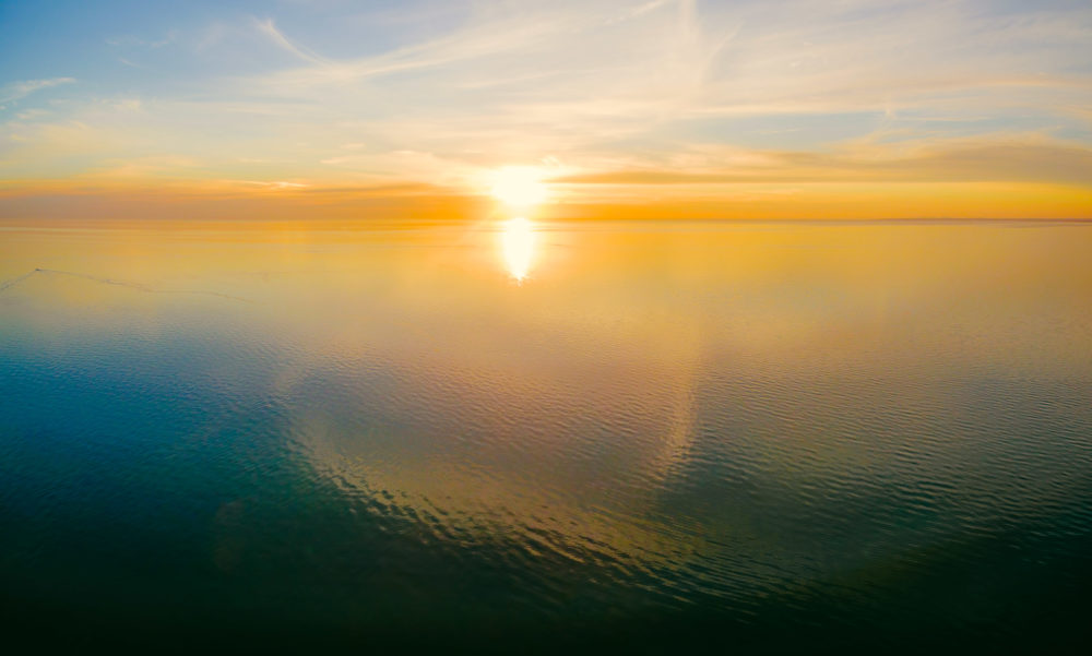 Aerial panoramic seascape - setting sun over calm water with cloud reflections and beautiful glowing colors